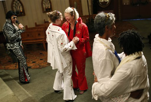 Sari Van Poelje, in red, dances with Katharina during their commitment ceremony given by Elvis tribute artist Michael Conti, left, at the Viva Las Vegas Wedding Chapel in Las Vegas  (AP Photo/John Locher, File)