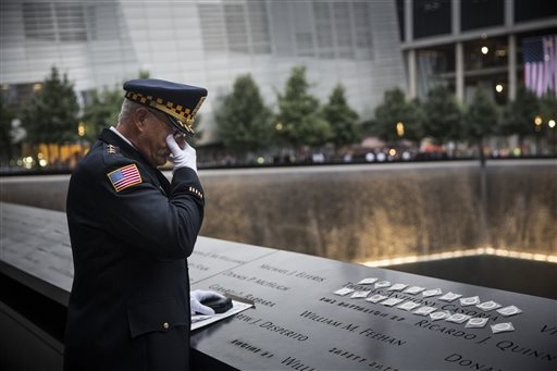 Sam Pulia, mayor of Westchester, Ill., and a former police officer of the same town, mourns over the name of his cousin, New York firefighter Thomas Anthony Casoria, who was killed in the South Tower in the attacks of Sept. 11, 2001, prior to the the memorial observances held at the site of the World Trade Center in New York, Thursday  (AP Photo/Andrew Burton, Pool)