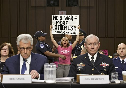 Members of the anti-war activist group CodePink interrupt a Senate Armed Services Committee hearing with Defense Secretary Chuck Hagel, left, and Army Gen. Martin Dempsey, chairman of the Joint Chiefs of Staff, on Capitol Hill   (AP Photo/J. Scott Applewhite)