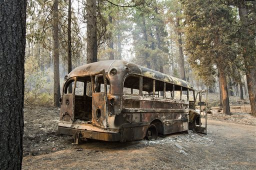 A burned out bus is shown near one of several homes that burned in the recent King fire near Icehouse in El Dorado County  (AP Photo/The Sacramento Bee, Randall Benton)