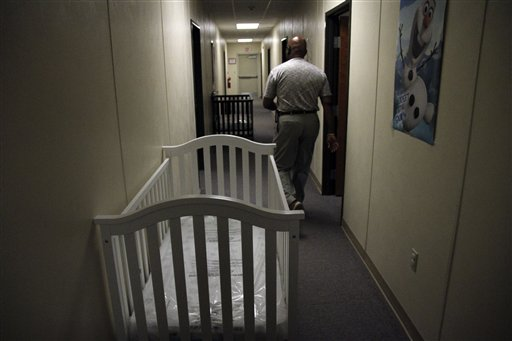 A federal employee walks past cribs inside of the barracks for law enforcement trainees turned into immigrant detention center  (AP Photo/Juan Carlos Llorca)