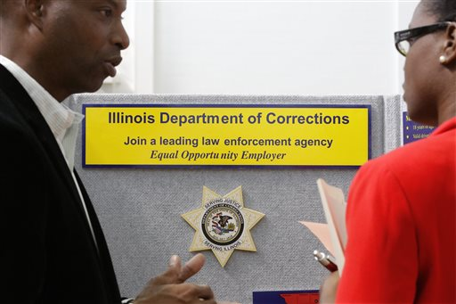 Illinois Department of Corrections employment recruiter, Forrest Ashby, left, speaks to students attending The Foot in the Door Career Fair at the University of Illinois in Springfield, Ill. (AP Photo/Seth Perlman)