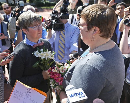 Nicole Pries, left, and Lindsey Oliver exchange vows Monday as the couple become one of the first same-sex couples in Virginia to be married,  outside a Richmond Court building in Richmond, Va.   (AP Photo/Steve Helber)