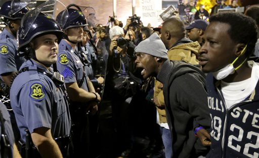 A protester yells at a Missouri State Police officer during a protest at the Ferguson, Mo., police headquarters Friday  (AP Photo/Charles Rex Arbogast)