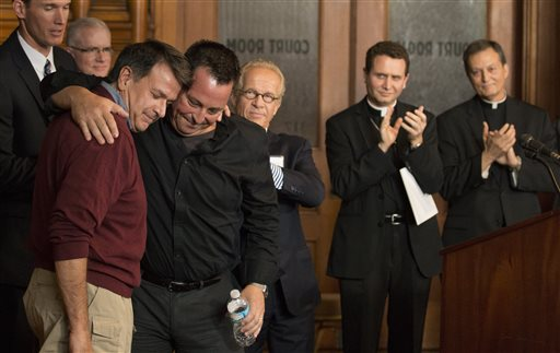 Abuse survivors Al Michaud, left, and Jim Keenan embrace after they both spoke of the importance of this historic agreement as attorney Jeff Anderson, Bishop Andrew Cozzens and Vicar General Rev. Charles Lachowitzer at right look on in St. Paul, Minn., Monday  (AP Photo/The Star Tribune, Brian Mark Peterson)