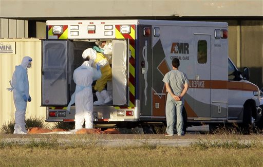 Medical staff in protective gear escort Nina Pham, exiting the ambulance, to a nearby aircraft at Love Field, Thursday  (AP Photo/Tony Gutierrez)