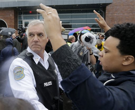 A police officer looks back for help as he tries to keep protesters from advancing farther into the parking lot at the Ferguson, Mo., police station (AP Photo/Charles Rex Arbogast)