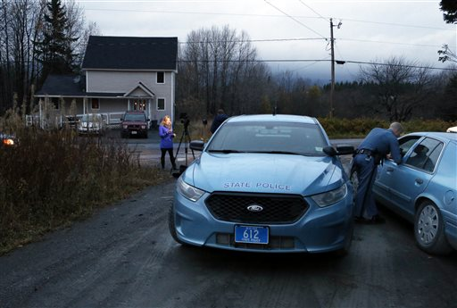 State troopers and a television reporter stand across from the home where Kaci Hickox, a nurse who treated Ebola patients in West Africa, is staying (AP Photo/Robert F. Bukaty)