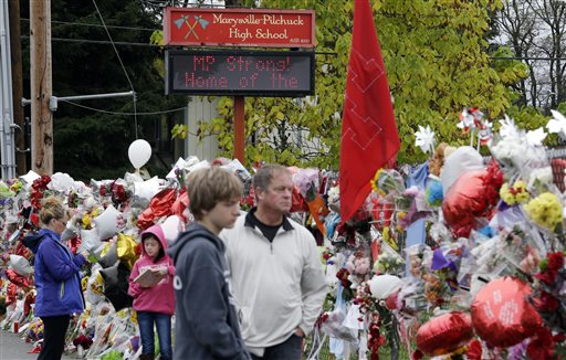 Gay Soriano, left, talks with daughter Gabby, 11, as her brother Titan, 13, and father Rick walk nearby and along a memorial for victims of a deadly school shooting nearly a week earlier  (AP Photo/Elaine Thompson)