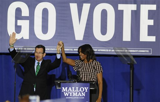 First lady Michelle Obama, right, holds hand with Connecticut Gov. Dannel P. Malloy, during a rally to support Malloy  (AP Photo/Jessica Hill)
