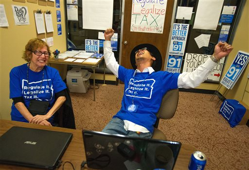 Matthew Yook, a field organizer for Measure 91, celebrates early returns that favor the Oregon Legalized Marijuana Initiative with Elvy Musikka, a medical marijuana recipient, at their downtown headquarters in Eugene, Ore. (AP Photo/The Register-Guard, Brian Davies)