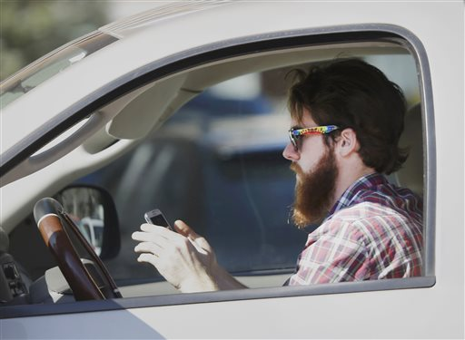 A man uses his cell phone as he drives through traffic in Dallas (AP Photo/LM Otero)