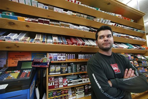 Brian Vincent poses in front of a large display of tobacco products at Vincent's Country Store in Westminster, Mass. (AP Photo/Elise Amendola)