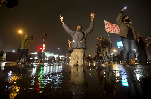 Anthony Grimes kneels on a rain-soaked street as he blocks traffic with other protesters  (AP Photo/David Goldman)