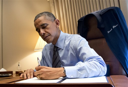 President Barack Obama signs two presidential memoranda associated with his actions on immigration in his office on Air Force One as he arrives at McCarran International Airport in Las Vegas, Friday  (AP Photo/Carolyn Kaster)