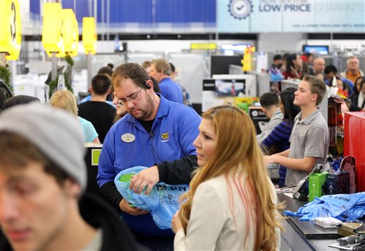 Cashier Ryan Gray helps customers during a Thanksgiving day sale at a Best Buy store in Broomfield, Colo., on Thursday  (AP Photo/Brennan Linsley)