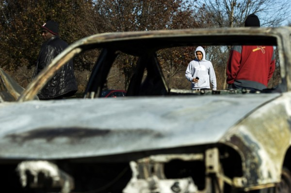 People walk towards a car lot where several cars had been burned and damaged following a night of rioting in Ferguson, Missouri