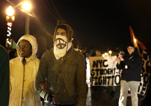 Protesters march down the streets near Ferguson Police Department Friday in Ferguson, Mo.  (AP Photo/Jeff Roberson)