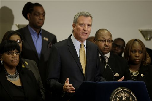 New York City Mayor Bill de Blasio, surrounded by community leaders, speaks to reporters about the grand jury's decision in the Eric Garner case in the borough of Staten Island in New York  (AP Photo/Seth Wenig)