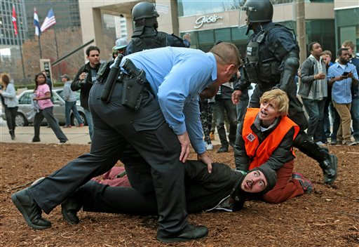 A clergy member assists a protester as he is taken to the ground on Sunday at Kiener Plaza. (AP Photo/St. Louis Post-Dispatch, Laurie Skrivan)