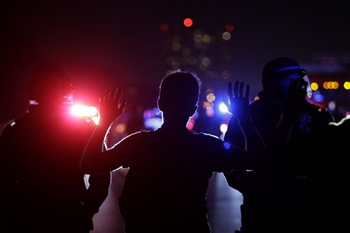 Protester raises his arms as California Highway Patrol Officers stand in front of him blocking traffic on Highway 80 in Berkeley, Calif. (AP Photo/Jeff Chiu)