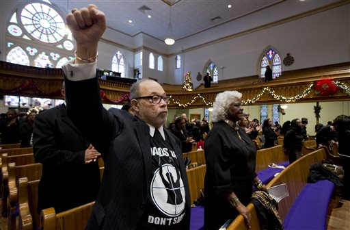 """Senior Judge Theodore Newman, of the Historic Courthouse, wearing a """"Hands Up, Don't Shoot"""" shirt, raises his clenched fist during a church service at the African Methodist Episcopal Church in Washington, Sunday  (AP Photo/Manuel Balce Ceneta)"""