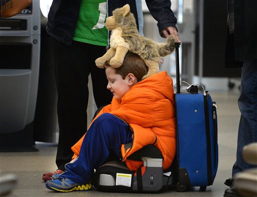 """David Welborn, 7, sits in the lost luggage line at the Delta Airlines desk at RDU International Airport on Tuesday, Dec. 23, 2014.  With his trusty dog """"Wolfbaby"""" perched on his head, he was with his mother and about 15 other people trying to find their bags after a cross country flight from Washington State. They were headed to Kinston, N.C. for the holidays.  (AP Photo/The News & Observer, Chuck Liddy)"""