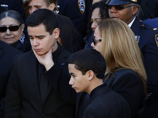 Justin Ramos, the son of slain New York City police officer Rafael Ramos, left, is comforted by his mother, Maritza Ramos, following funeral services at Christ Tabernacle Church, in the Glendale section of Queens, Saturday (AP Photo/Julio Cortez)