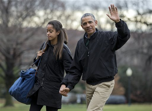 President Barack Obama, right, with his daughter Malia Obama, waves as they arrive at the White House in Washington, Sunday  (AP Photo/Manuel Balce Ceneta)