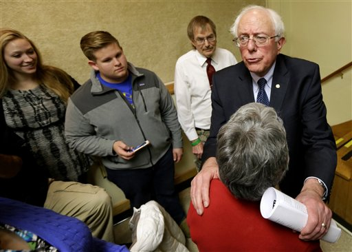 Sen. Bernie Sanders, I-Vt., right, talks with local residents after a town hall meeting in Ames, Iowa.  (AP Photo/Charlie Neibergall)