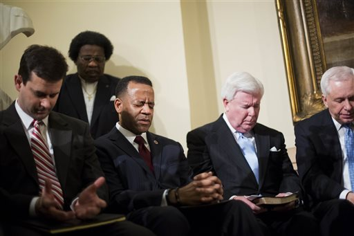 Former Atlanta fire chief Kelvin Cochran, third from right, observes a moment of prayer as religious groups rally to support him following his termination in Atlanta. (AP Photo/David Goldman, File)