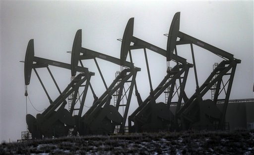 Oil pump jacks work in unison, in Williston, N.D.  (AP Photo/Eric Gay)