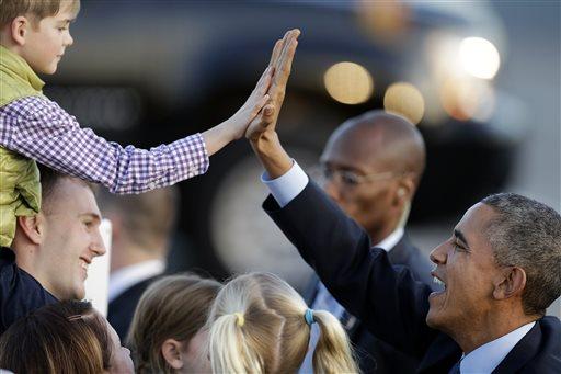 President Barack Obama high five's a boy upon his arrival at San Francisco International Airport. (AP Photo/Ben Margot)