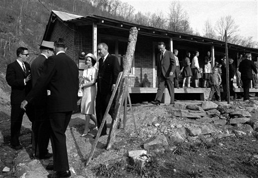 President Lyndon B. Johnson and his wife leave the home of Tom Fletcher, father of eight, who told Johnson he had been out of work for nearly two years, in Inez, Ky. (AP Photo/File)