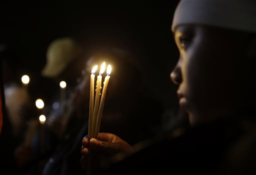 Chaunte Williams, 13, holds up three candles as she takes part in a vigil Thursday in Ferguson, Mo.  (AP Photo/Jeff Roberson)