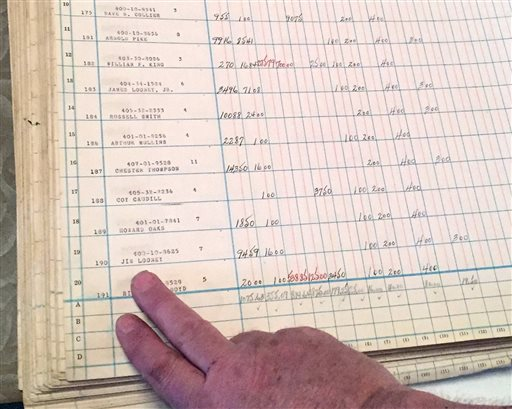 Jack Looney points to an entry in an old mining company ledger at his Highland Winery in Seco, Ky. (AP Photo/Ben Gish)