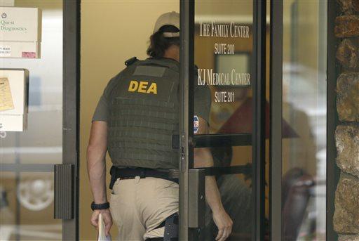 A Drug Enforcement Administration officer walks into a medical clinic in Little Rock, Ark. (AP Photo/Danny Johnston)