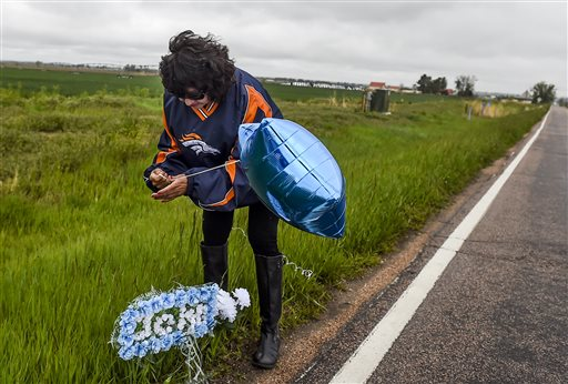 Cora Rogakis sets up a memorial for John Jacoby in Windsor, Colo. (Erin Hull/The Coloradoan via AP)