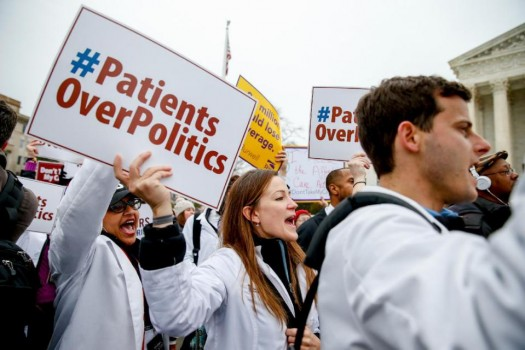 Demonstrators rally outside the Supreme Court in Washington, as the court was hearing arguments in President Barack Obama's health overhaul. (AP Photo/Andrew Harnik)