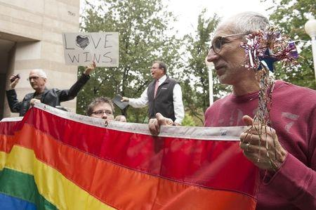 Larry Ferri (R) and Brandi Morris (C) hold large rainbow flag as gay couples marry outside of Mecklenburg County Register of Deeds office in Charlotte, North Carolina. (REUTERS/Davis Turner)