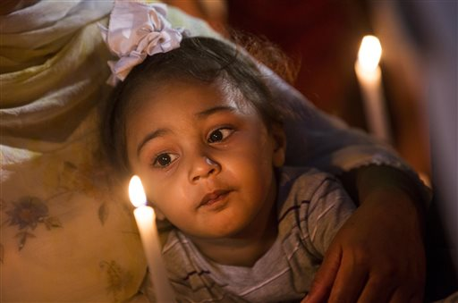 A child looks at a candle during a vigil at the Oak Creek Civic Center in Oak Creek, Wis. for the victims of a mass shooting at the Sikh Temple of Wisconsin. (AP Photo/Tom Lynn)