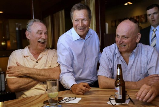 Republican Ohio Gov. John Kasich, center, greets patrons at a bar in a restaurant in Nashua, N.H.  (AP Photo/Steven Senne)