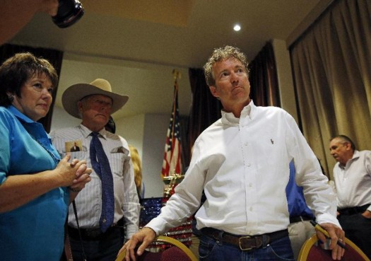 Republican presidential candidate Sen. Rand Paul, R-Ky., right, meets with people during a political event in Mesquite, Nev. Carol Bundy, left, and Cliven Bundy, in cowboy hat, stand nearby. (AP Photo/John Locher)