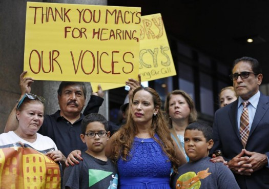 Vicente Mayorga, left, holds a sign next to Dominican immigrant Angela Lopez, front center, of Long Island, N.Y., as she stands with her sons Gabriel, left, and Adrian in front of Macy's Herald Square flagship store. (AP Photo/Kathy Willens)