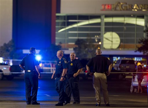 Law enforcement personnel stand near a police line at The Grand Theatre following a deadly shooting in Lafayette, La. (Paul Kieu/The Daily Advertiser via AP)
