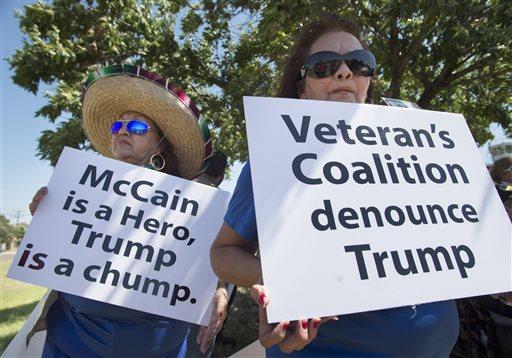 Lourdes Galvan, left, and Irma Vargas, both of San Antonio, Texas, hold signs denouncing Republican presidential contender Donald Trump, Thursday, July 23, 2015, at Laredo International Airport in Laredo, Texas. (AP Photo/Darren Abate)