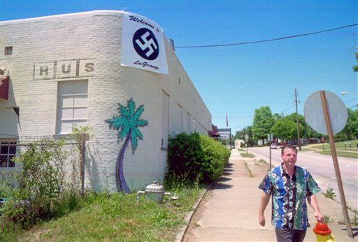 "In this April 27, 2001 photo, Pub owner John Russell Houser walks down a street under a banner he is displaying to compare a recent LaGrange City Council decision to pull his alcohol license to Nazi tactics. Houser, 59, stood up about 20 minutes into the ""Trainwreck"" movie and fired first at two people sitting in front of him, then aimed his handgun at others Thursday, July 23, 2015, Police said Friday they found 13 shell casings.(Nat Gurley/LaGrange Daily News via AP)"