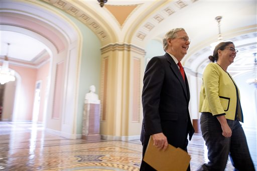 Senate Majority Leader Mitch McConnell, R-Ky., left, accompanied by Secretary for the Majority of the Senate Laura Dove, heads into the Senate chamber as the Senate convenes for a Sunday session on Capitol Hill in Washington, Sunday, July 26, 2015. On the agenda are efforts to repeal President Barack Obama's health care law and reviving the federal Export-Import Bank. (AP Photo/Andrew Harnik)