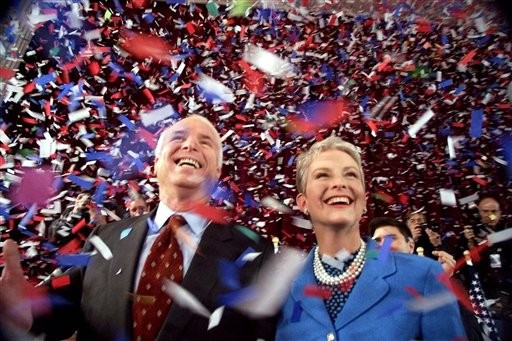 FILE  - In this Jan. 30, 2000, file photo, then-Republican presidential candidate Sen. John McCain, R-Ariz., and his wife Cindy, smile as confetti falls on them at the end of their 114th New Hampshire town hall meeting with voters at the Peterborough Town House in Peterborough, N.H. Peterborough was the sight of McCain's first town hall meeting in April 1999.  It was the summer of 1999, and McCain didn't have many big names on the side of his campaign for president. He didn't have much money or decent crowds, and even resorted at one point to giving away ice cream to lure voters to an event. Enter the town hall. McCain will be back in New Hampshire on Aug. 1 campaigning for friend and fellow Sen. Lindsey Graham at a town hall. (AP Photo/Stephan Savoia, File)