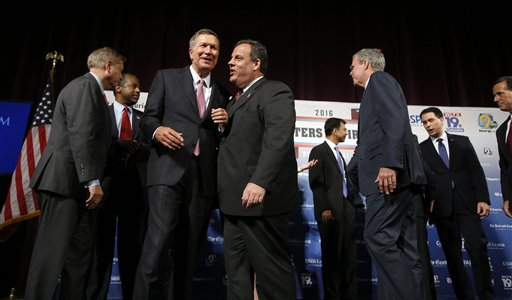 Republican presidential candidates, from left, Lindsey Graham, Ben Carson, John Kasich, Chris Christie, Bobby Jindal, Jeb Bush, Scott Walker and Rick Santorum speak among themselves after a forum Monday, Aug. 3, 2015, in Manchester, N.H. (AP Photo/Jim Cole)